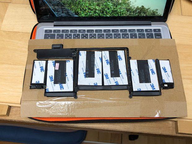 届いたバッテリーの背面。固定するための両面テープがついている。